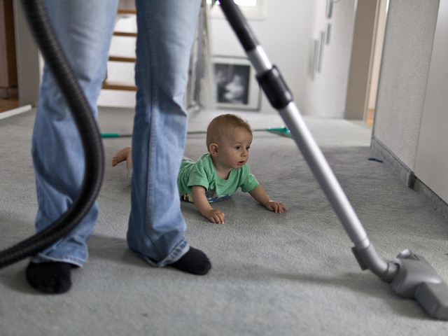 A mother hoovers the carpet while her six-months-old baby is watching, pictured on September 16, 2011, in Unterfelden in the