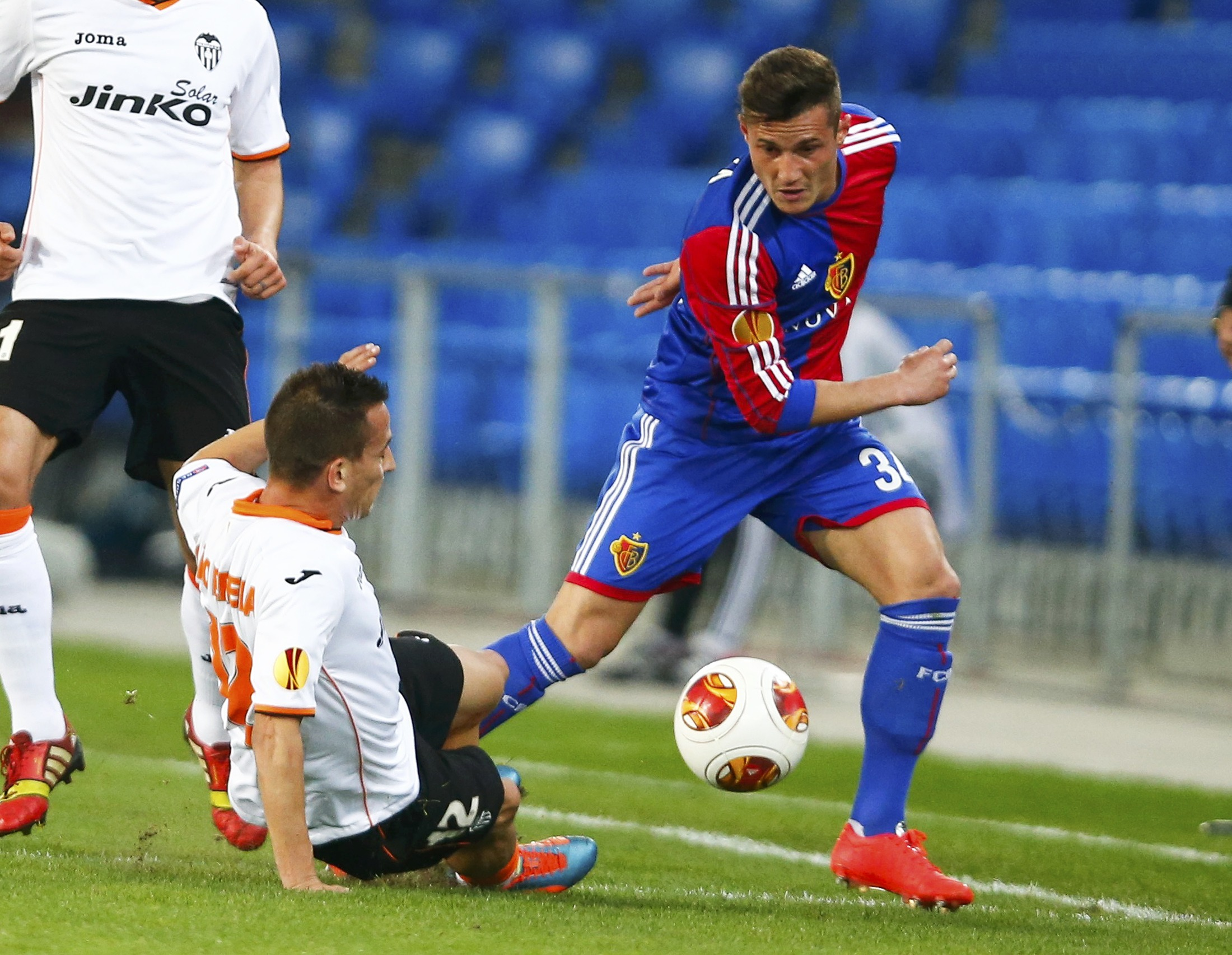 Valencia's Joao Pereira fights for the ball with FC Basel's Taulant Xhaka (R) during their Europa League quarter-final first leg soccer match in St.Jakob-Park stadium in Basel, April 3, 2014.  REUTERS/Arnd Wiegmann (SWITZERLAND  - Tags: SPORT SOCCER)