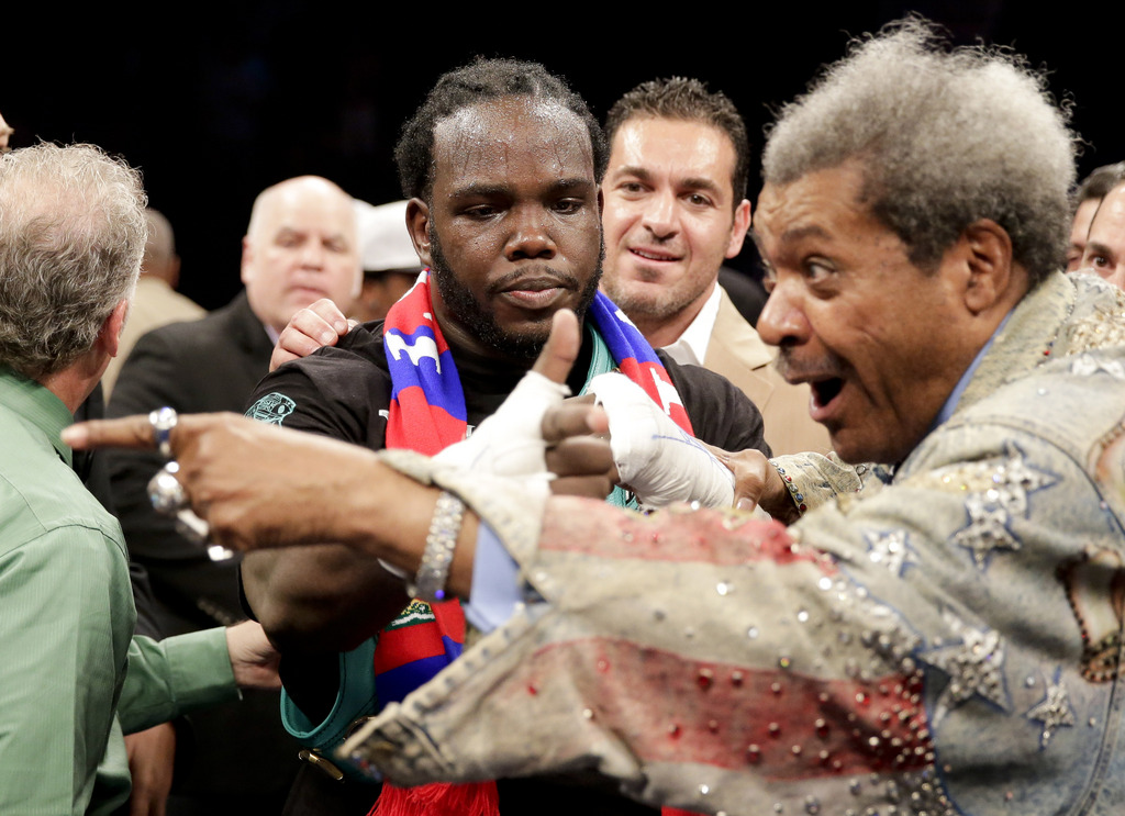 Bermane Stiverne, center, celebrates his win over Chris Arreola with promoter Don King after a rematch for the WBC heavyweight boxing title in Los Angeles, Saturday, May 10, 2014. ()