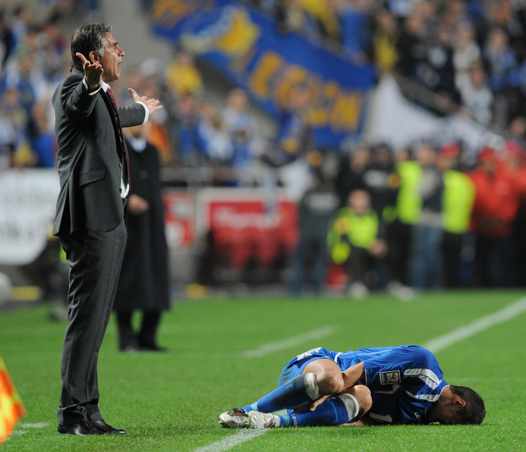 Portugal's coach Carlos Queiroz, left, reacts as Bosnia-Herzegovina's Sejad Salihovic grimaces in pain on the pitch during their World Cup qualifying playoff first leg soccer match Saturday, Nov. 14, 2009, at the Luz stadium in Lisbon, Portugal. Portugal