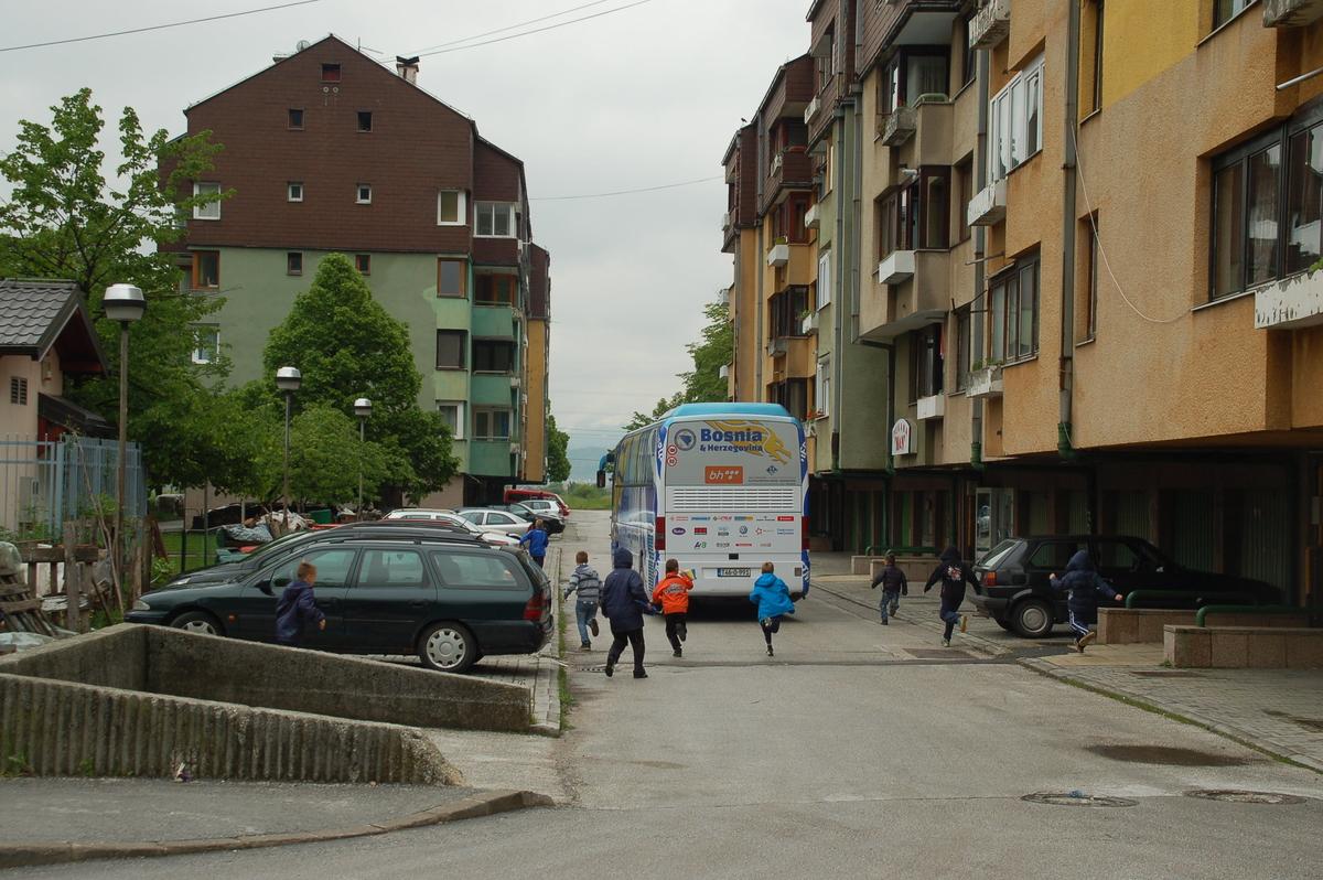 Kinder laufen dem Bus der Nationalmannschaft nach dem Training im Stadion Hrasnica hinterher.