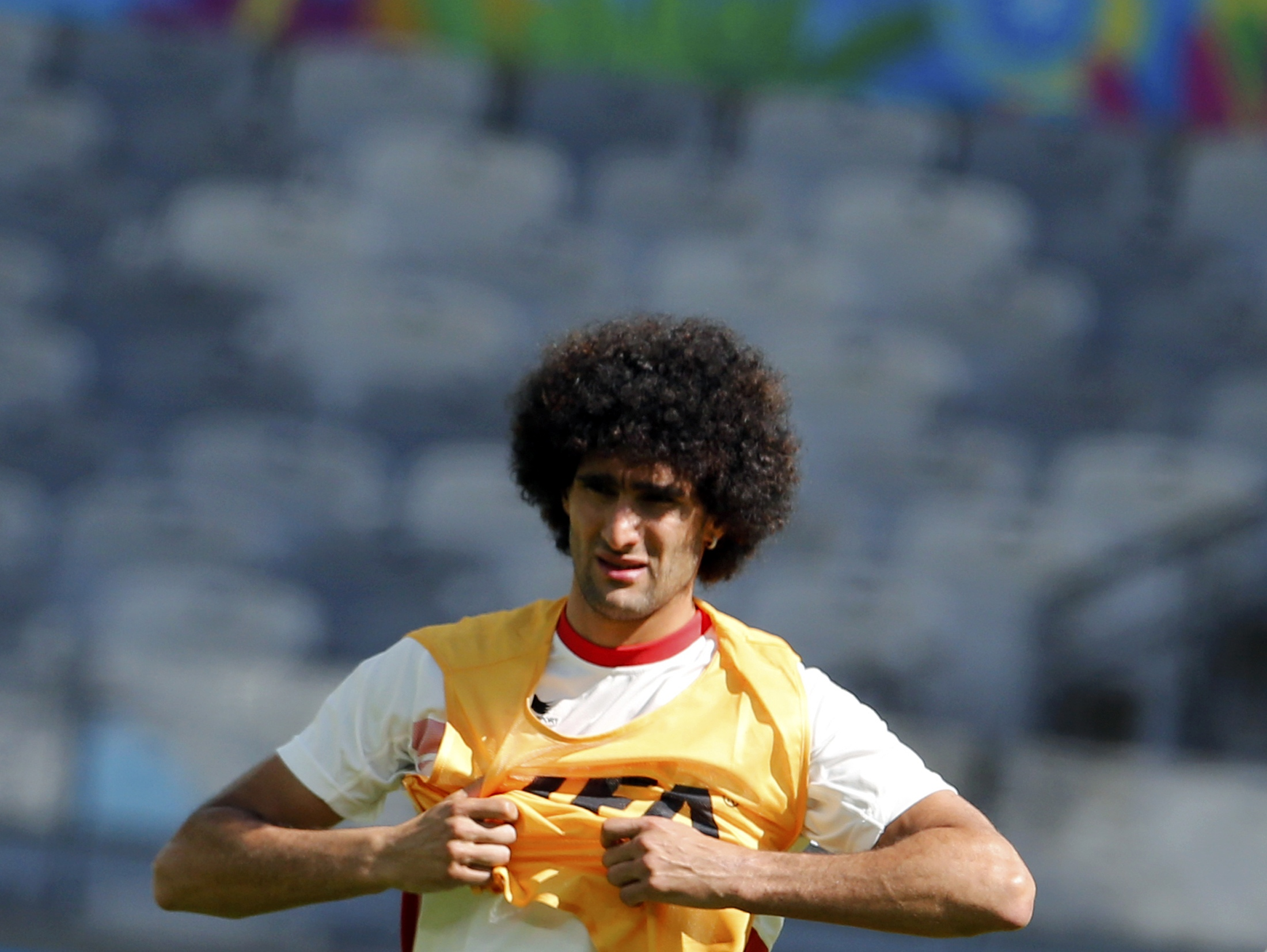 Belgium's national soccer team player Marouane Fellaini puts on a vest as he attends a training session at the Mineirao stadium in Belo Horizonte June 16, 2014. Belgium will face Algeria in their first 2014 World Cup Group H soccer match on June 17. REUTE