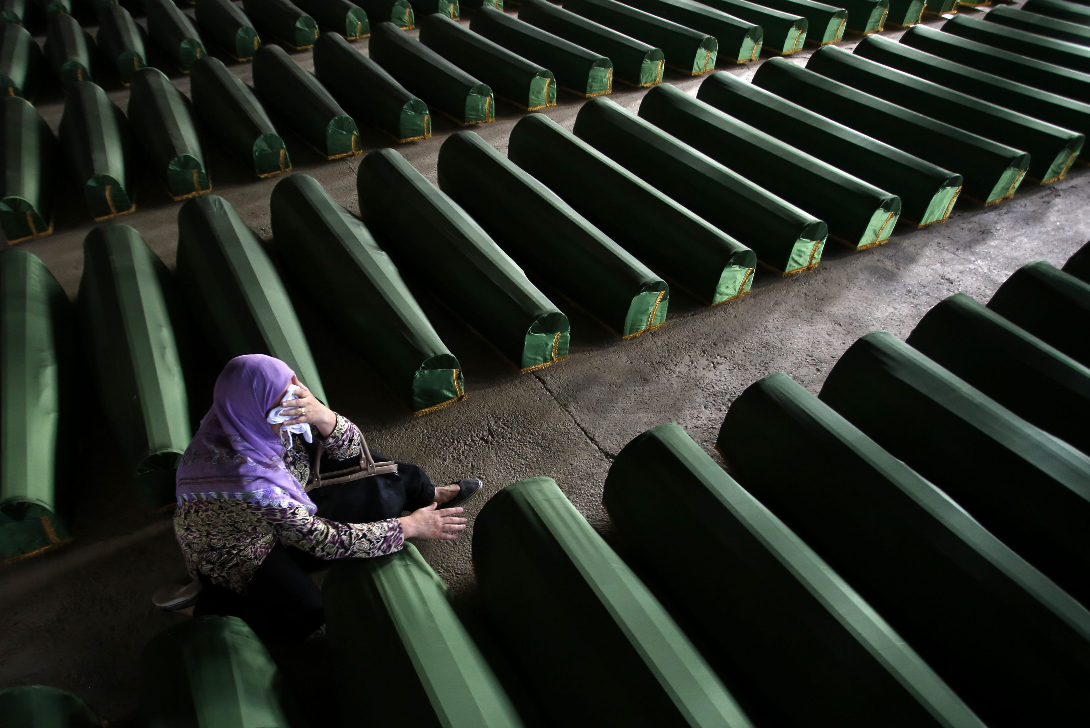 A Bosnian Muslim woman cries near coffin of a relative, which is one of the 175 coffins of newly identified victims from the 1995 Srebrenica massacre, in Potocari Memorial Center, near Srebrenica, July 10, 2014. Family members, foreign dignitaries and gue