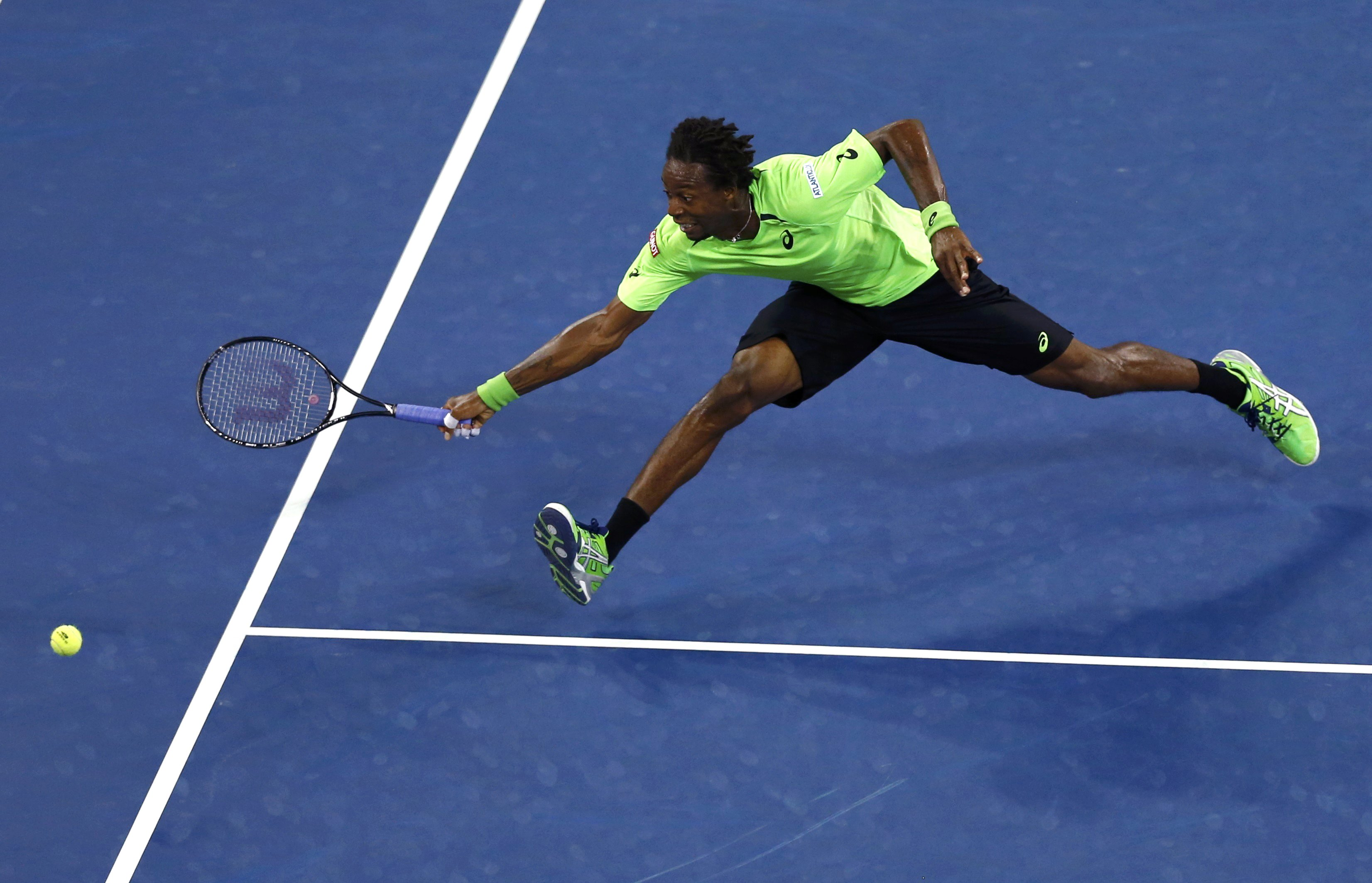 Gael Monfils of France stretches to try and make a return in the fourth set to Roger Federer of Switzerland during their quarter-final men's singles match at the 2014 U.S. Open tennis tournament in New York, September 4, 2014. REUTERS/Adam Hunger (UNITED