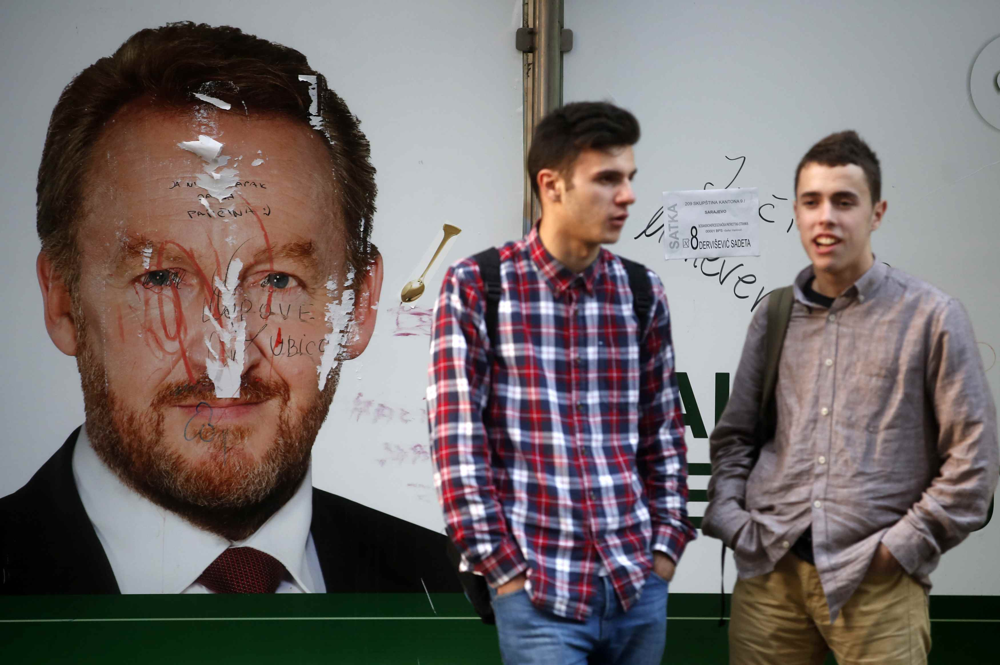 Men stand at a bus station in front of a defaced election poster in Sarajevo, October 10, 2014. Bosnians will vote on Sunday for a parliamentary and presidential election that could break the reform deadlock in the ethnically divided country or deepen div