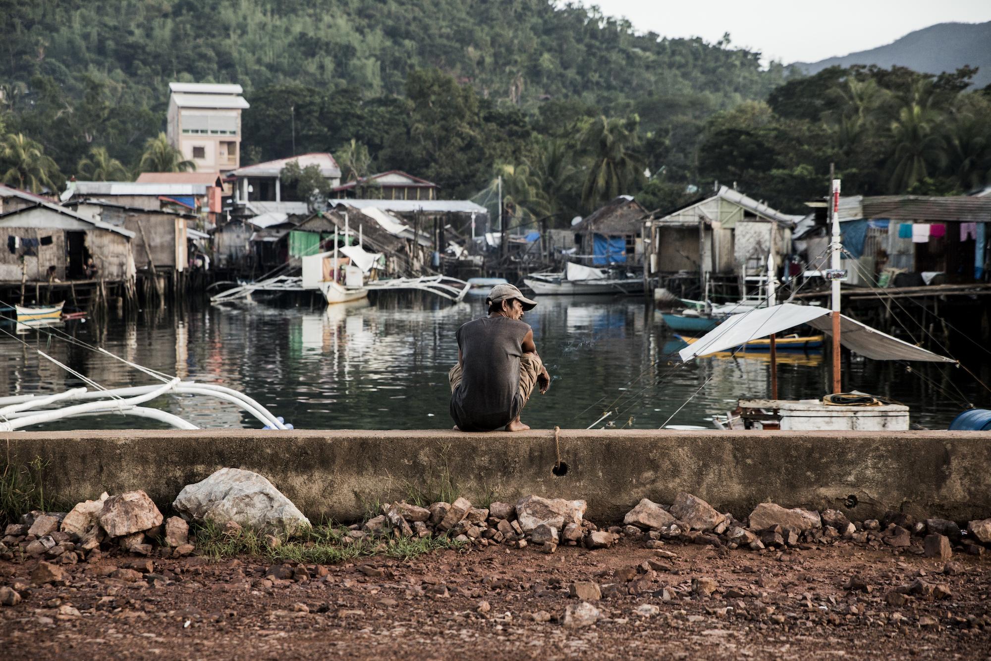 Ein Fischer ruht sich nach dem morgendlichen Fischmarkt auf einer Mauer aus. Vor ihm liegen die Pfahlbauten im Ufergebiet von Coron.