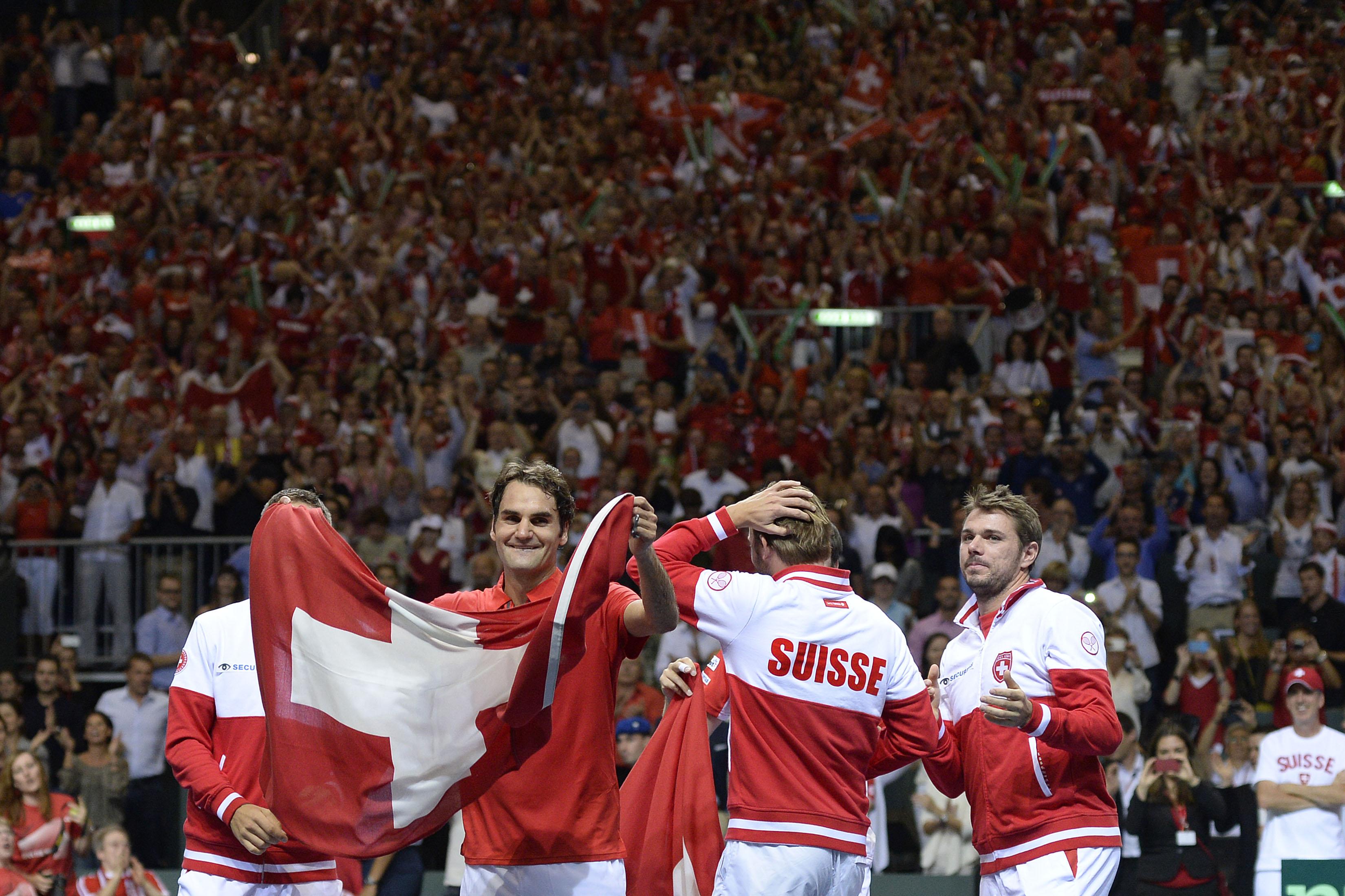 Im besten Fall fröhlicher Patriotismus: Die Schweiz gewinnt im Halbfinal von Genf gegen Italien. Roger Federer feiert mit Schweizerflagge und den Teamkollegen Marco Chiudinelli, Michael Lammer und Stan Wawrinka.