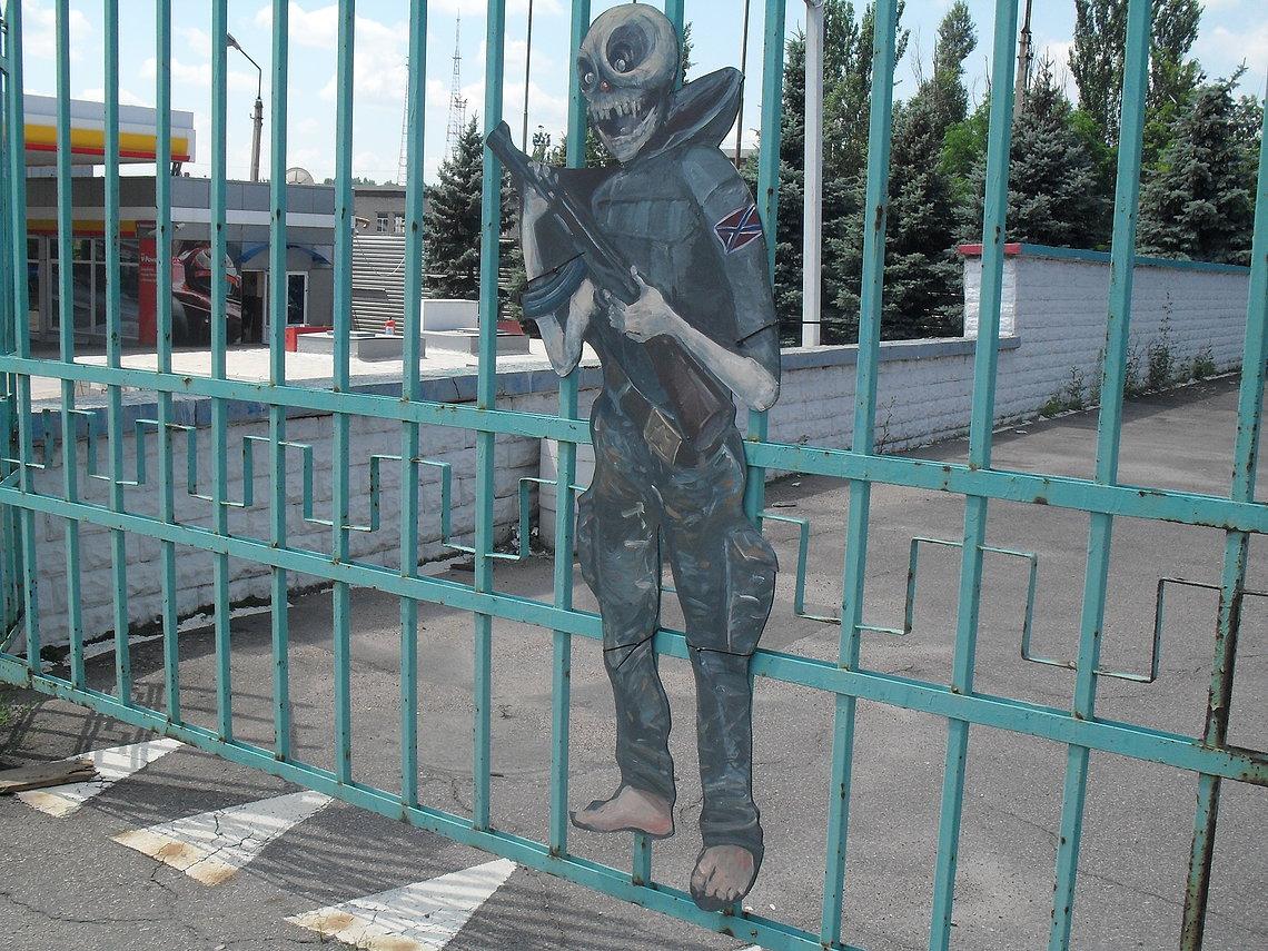 Ein Separatist mit Totenschädel. Die Figur wurde an das Tor eines großen Parkplatzes in Donezk montiert.