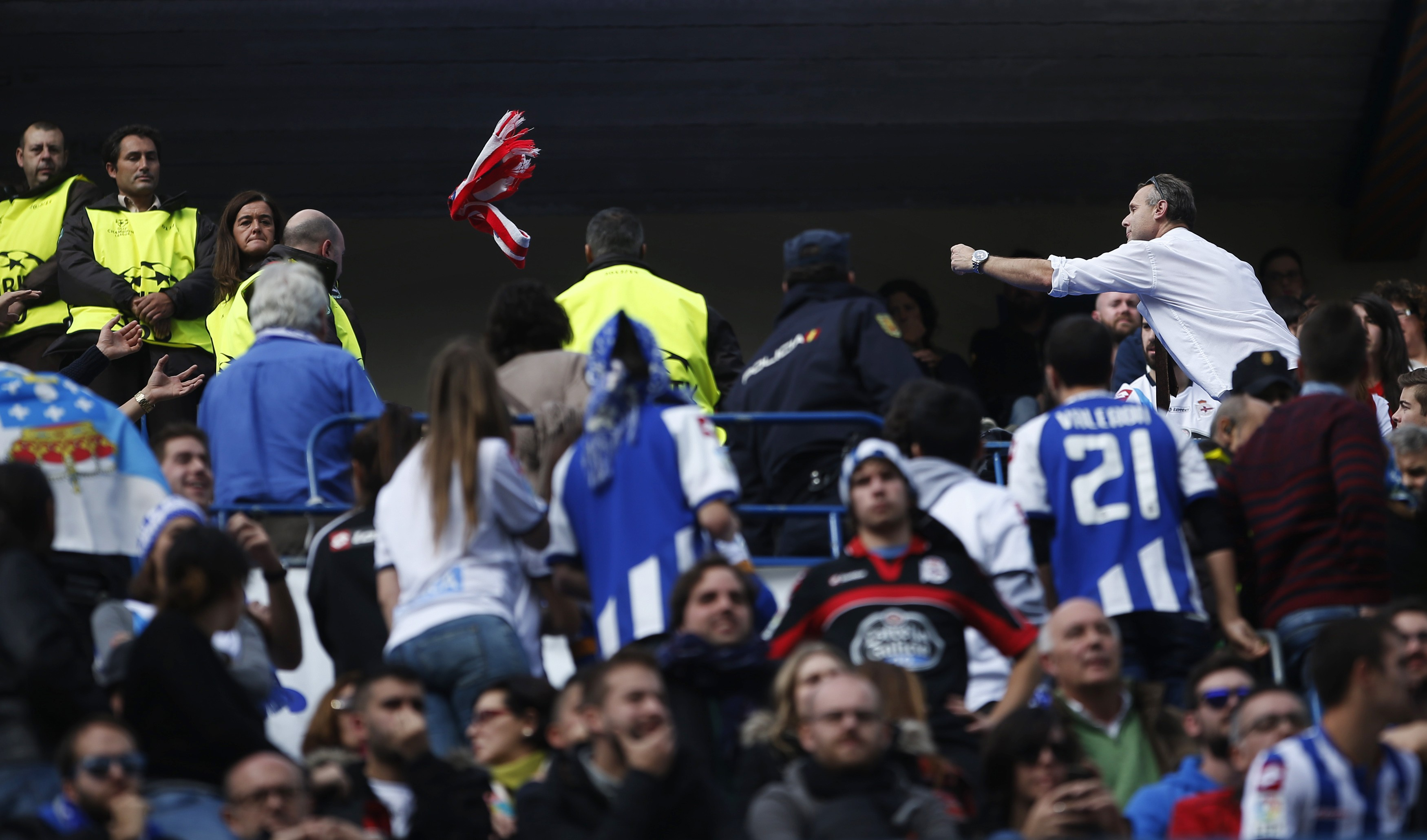 An Atletico Madrid fan (R) throws his team's scarf to Deportivo Coruna supporters during their Spanish first division soccer match at Vicente Calderon stadium in Madrid, November 30, 2014. A Deportivo La Coruna supporter was critically injured when dozens of rival fans clashed near the stadium before the club's La Liga match at Atletico Madrid on Sunday. REUTERS/Susana Vera (SPAIN - Tags: SPORT SOCCER)