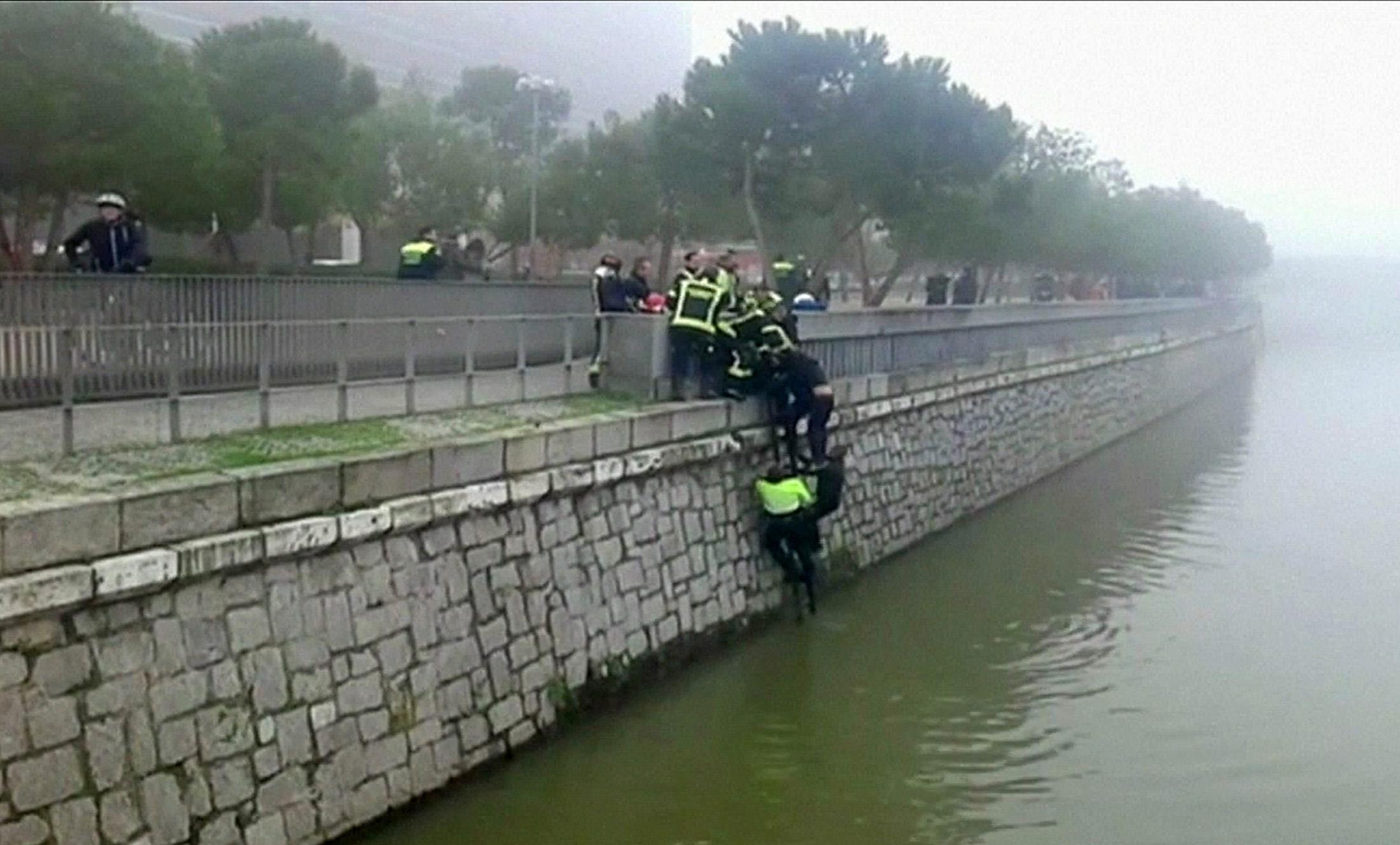 Helfer retten einen unbekannten Mann aus dem Fluss Manzanares in Madrid, wo in der Nähe des Stadions von Atletico gewalttätige Fangruppen sich eine Schlacht lieferten.