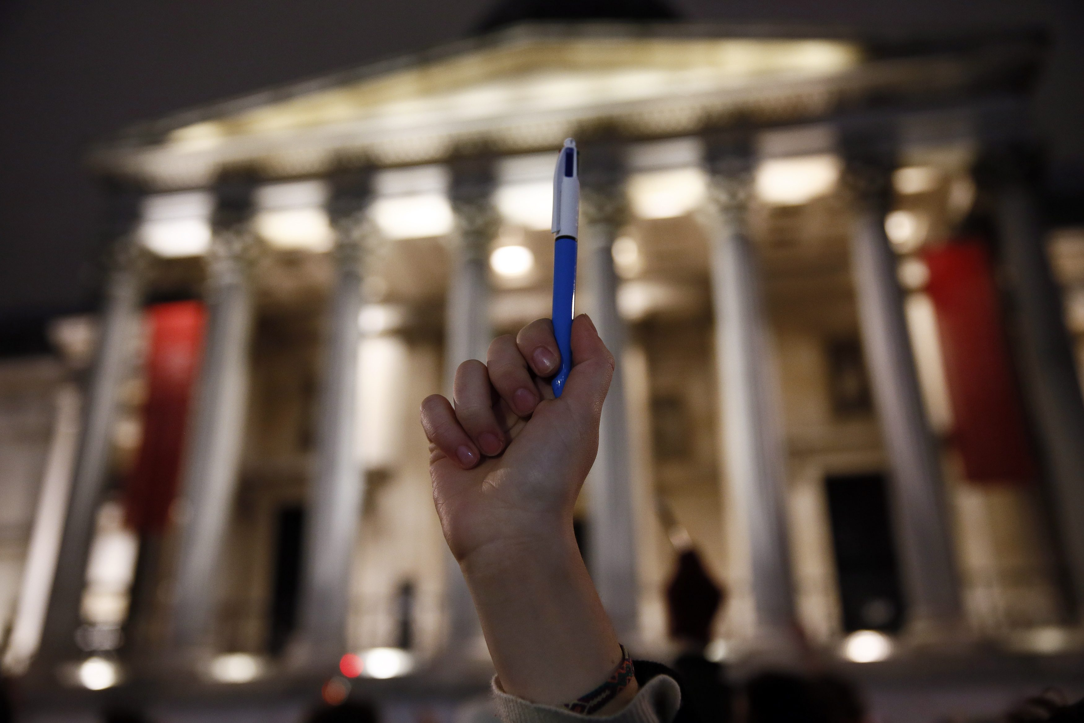 A woman raises a pen during a vigil to pay tribute to the victims of a shooting by gunmen at the offices of weekly satirical magazine Charlie Hebdo in Paris, at Trafalgar Square in London January 7, 2015. Hooded gunmen stormed the Paris offices of the weekly satirical magazine known for lampooning Islam and other religions, shooting dead at least 12 people, including two police officers, in the worst militant attack on French soil in decades. REUTERS/Stefan Wermuth (BRITAIN - Tags: POLITICS CRIME LAW CIVIL UNREST MEDIA)
