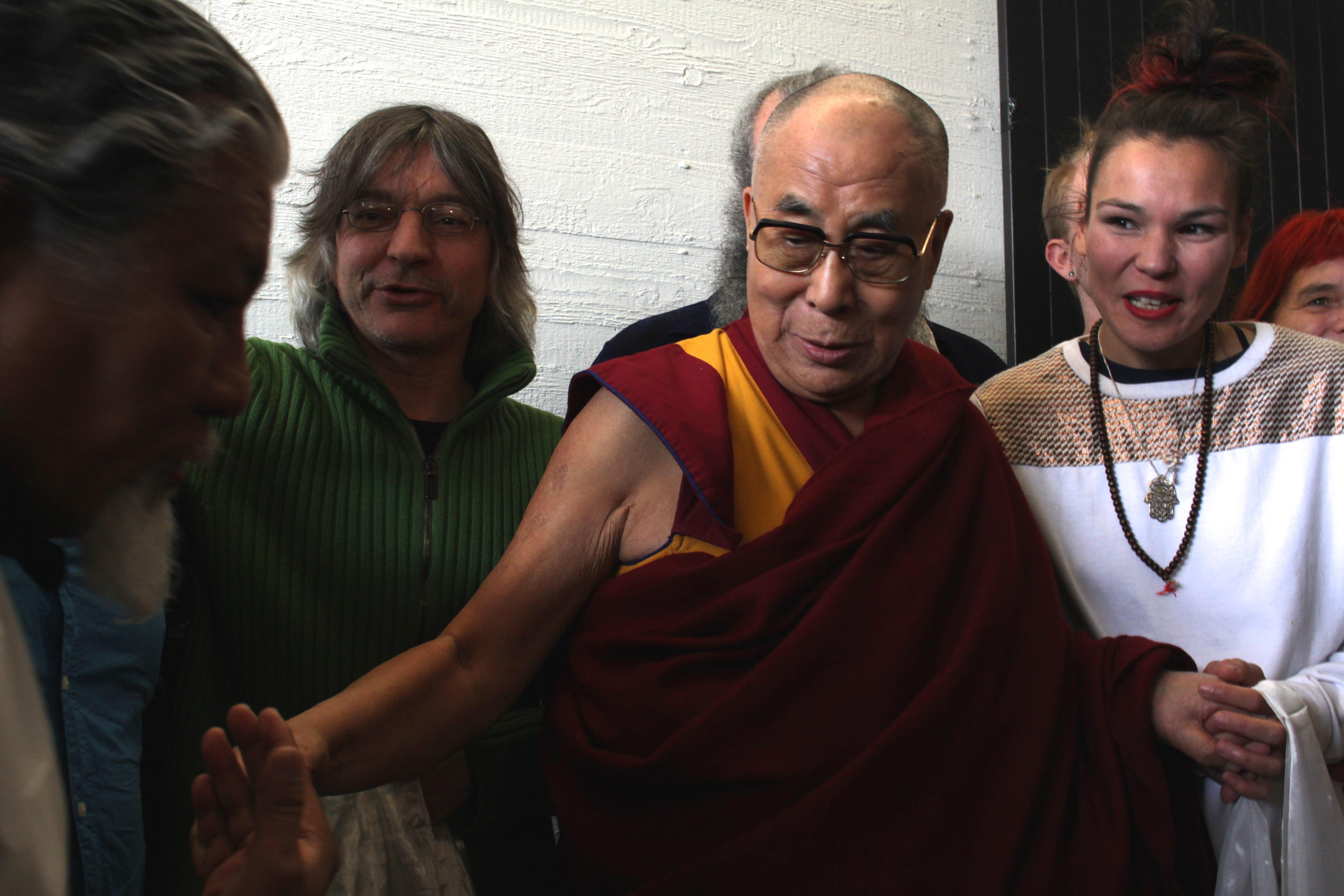 Loten Namling, Franz Treichler und Kate Wax posieren gemeinsam mit dem Dalai Lama für ein Erinnerungsfoto.