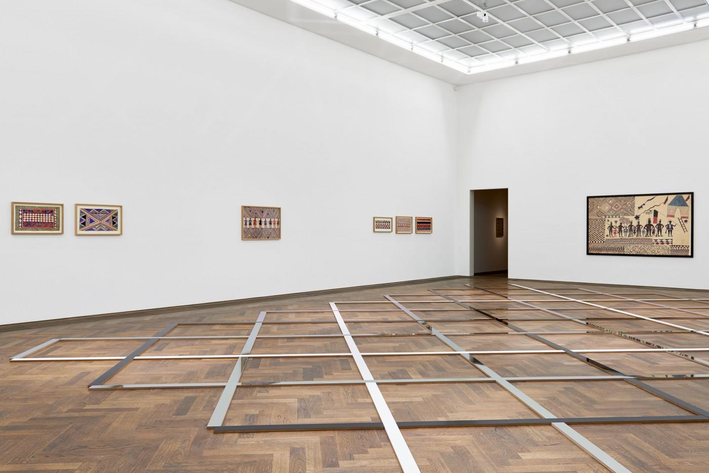 Die Installation am Boden nimmt die Boden- und Deckenstruktur wie auch die Muster in den Bildern von Thela Tendu auf.