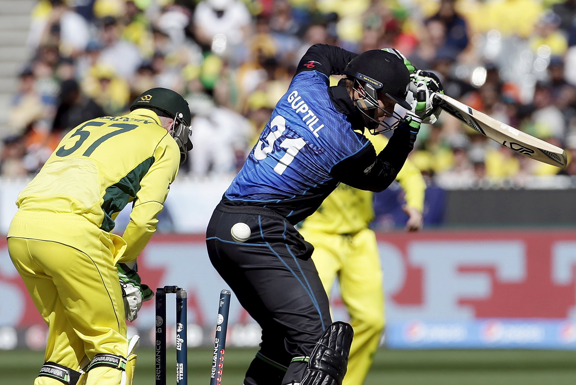 Australia's wicketkeeper Brad Haddin (L) watches as New Zealand's Martin Guptill (R) is bowled by Australia's Glenn Maxwell for 15 runs during their Cricket World Cup final match at the Melbourne Cricket Ground (MCG) March 29, 2015. REUTERS/Hamish Blair