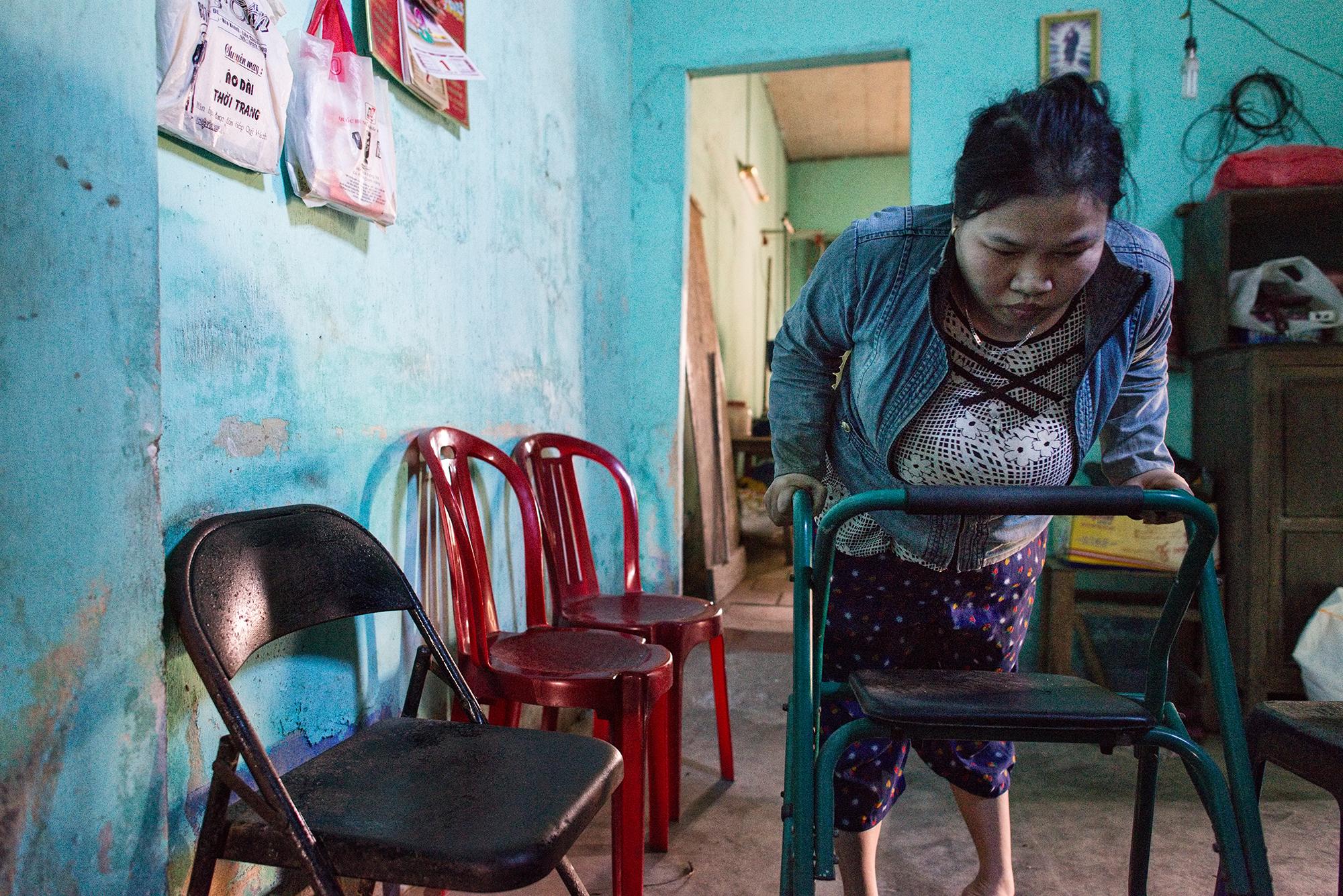 Agent-Orange-Opfer Tran Thi Ty Nga: Die 33-Jährige kann sich nur dank einem Rollator und der permanenten Hilfe ihrer Mutter etwas fortbewegen.