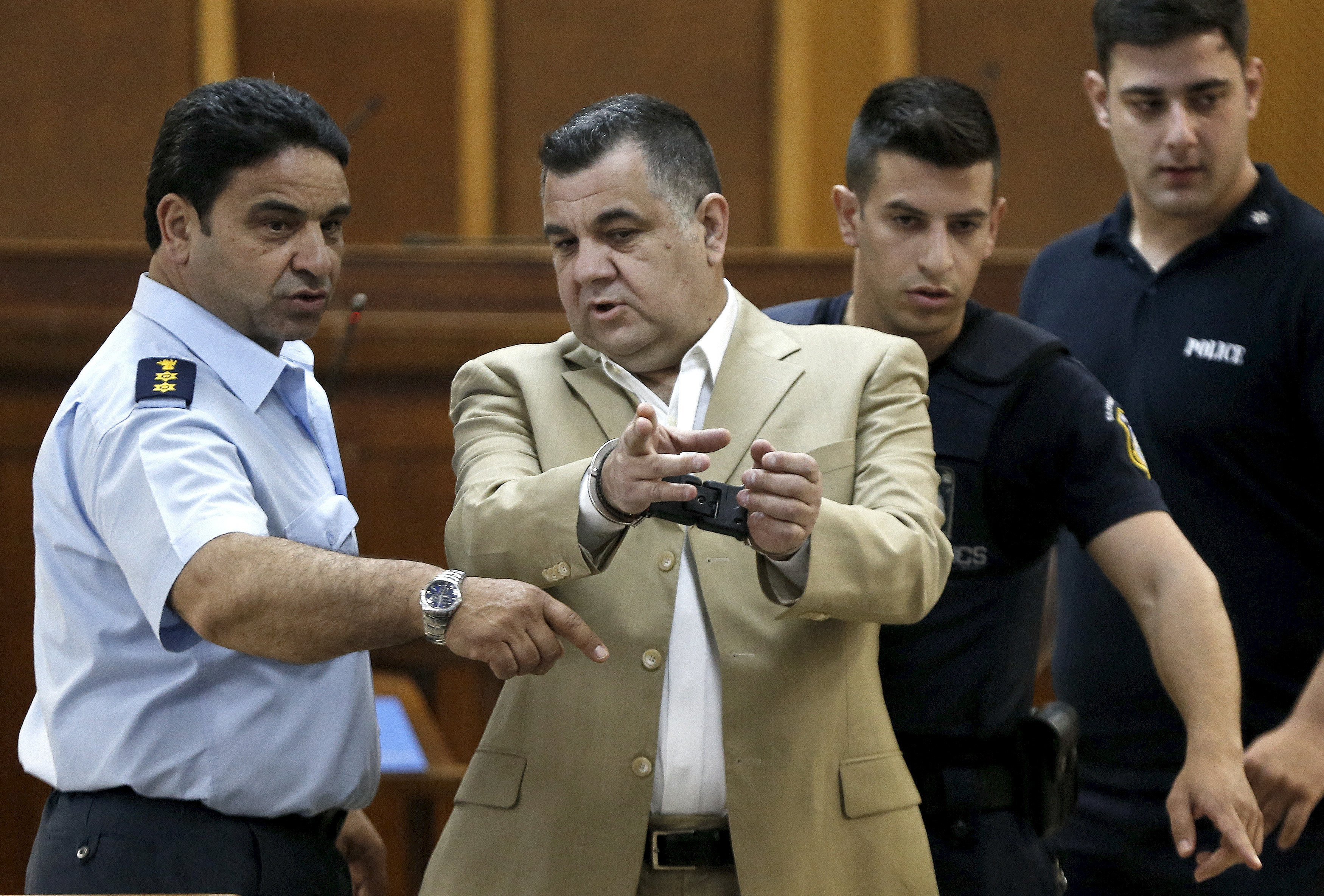 Giorgos Roupakias (C), who is in custody pending trial over the killing of anti-racism Greek rapper Pavlos Fissas, is escorted by police officers at the court room where the trial of members and leaders of Greece's far-right Golden Dawn party takes place, in Koridallos prison, near Athens, May 7, 2015. Party leader Nikos Mihaloliakos and more than a dozen top figures in Golden Dawn were arrested on charges of founding and participating in a criminal organisation following the killing of an anti-fascism rapper in 2013 by a party supporter. REUTERS/Alkis Konstantinidis