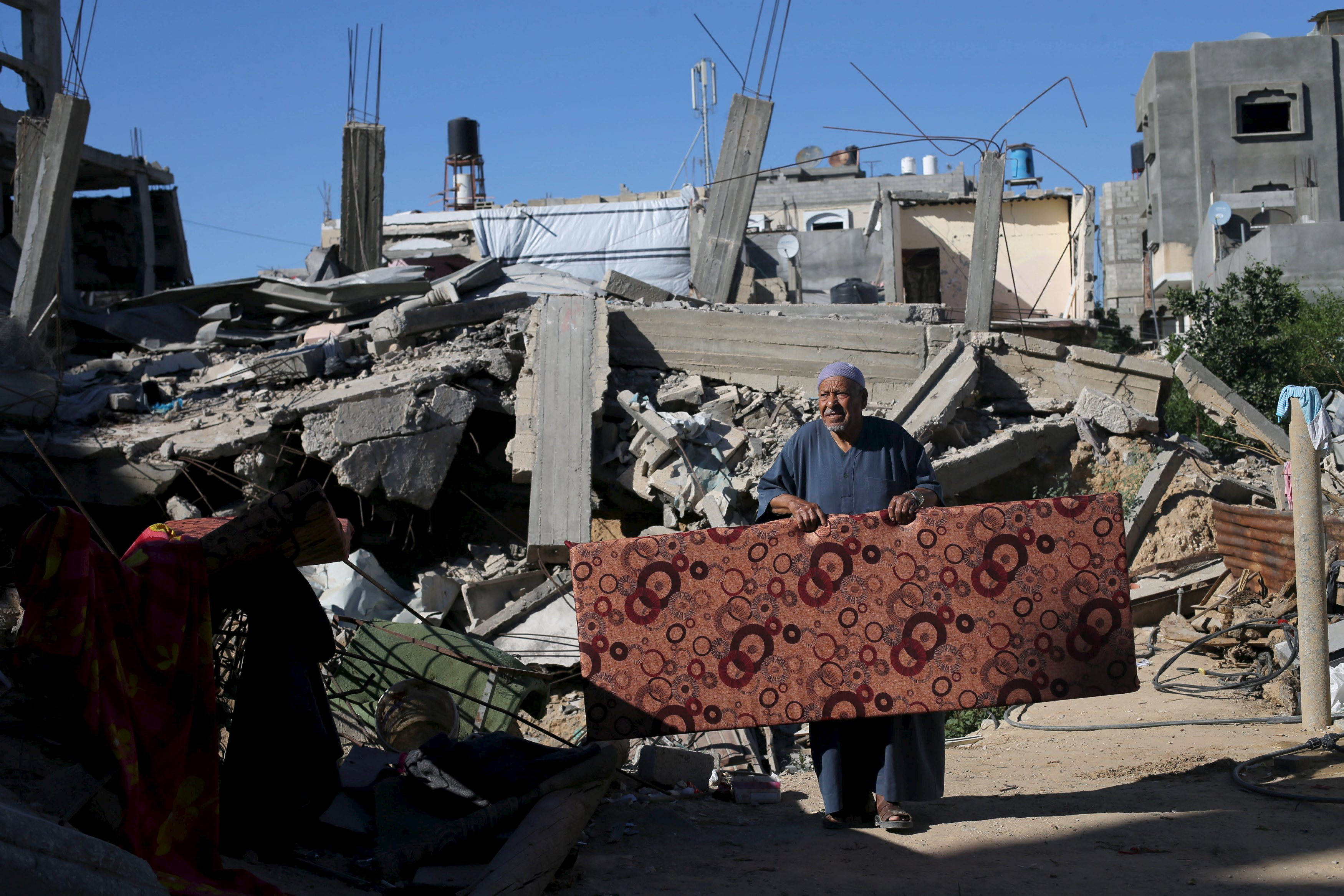 A Palestinian man carries a mattress outside his house that witnesses said was destroyed by Israeli shelling during a 50-day war last summer, in Khan Younis in the southern Gaza Strip June 22, 2015. Israel disputed on Monday the findings of a U.N. report that it may have committed war crimes in the 2014 Gaza conflict, saying its forces acted