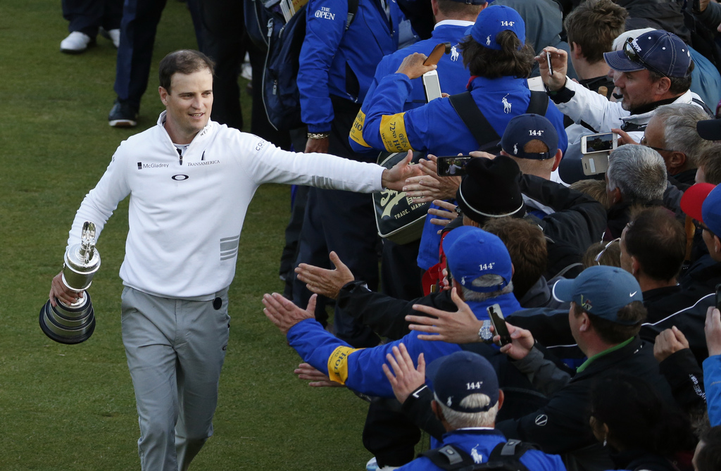 United States� Zach Johnson celebrates with members of the public as he holds the trophy after winning a playoff after the final round at the British Open Golf Championship at the Old Course, St. Andrews, Scotland, Monday, July 20, 2015. (AP Photo/Alastair Grant)