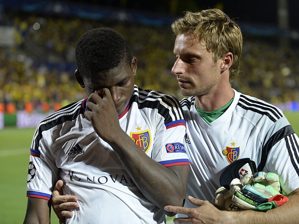 epa04898132 Basel's Breel Embolo (L) is comforted by team mate Germano Vailati after the UEFA Champions League play-off round second leg soccer match between Maccabi Tel Aviv FC and FC Basel 1893 at the Bloomfield stadium in Tel Aviv, Israel, 25 August 2015. Maccabi Tel Aviv won on away goals. EPA/GEORGIOS KEFALAS