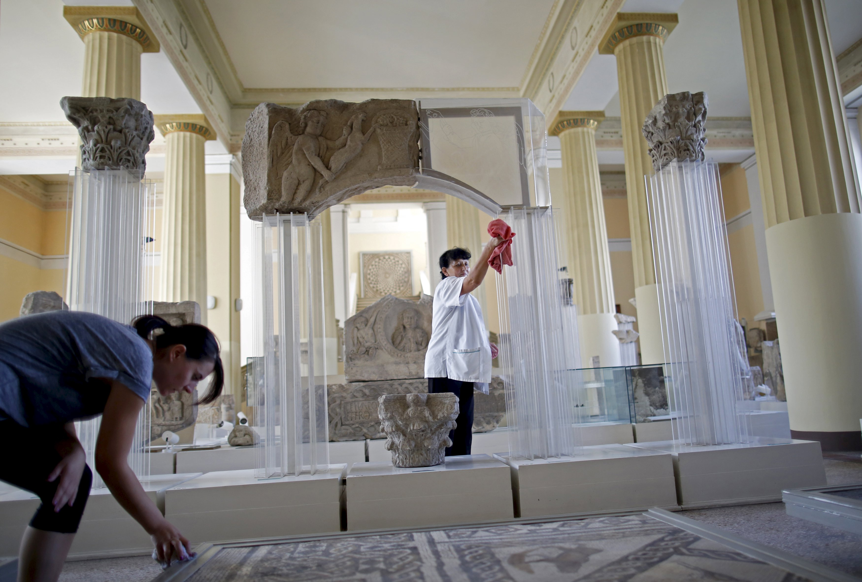 National Museum employees Ana Maric (L) and Djula Keric clean archaeological excavations in National Museum in Sarajevo, September 9, 2015. Employees at Bosnia's National Museum, known as the British Museum of the Balkans, returned to work on Wednesday to prepare for the re-opening of the institution which was closed three years ago over a lack of funding. The divided country's authorities have promised to provide funding for the Sarajevo landmark museum and open it on Sept. 15, following years of failed attempts to agree on how to finance it. REUTERS/Dado Ruvic