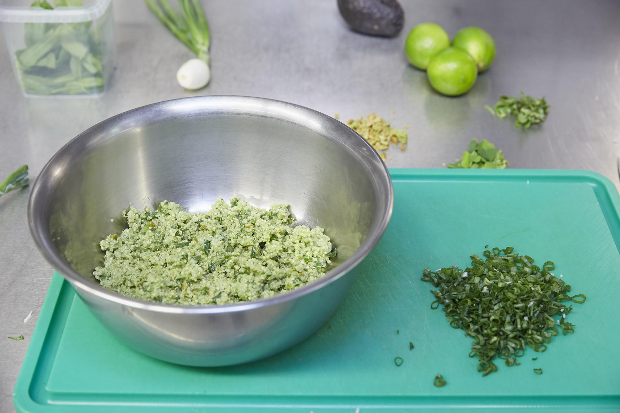 Nachdem der Quinoa-Salat abgekühlt ist, wird er mit gehackten Kräuter vermischt.