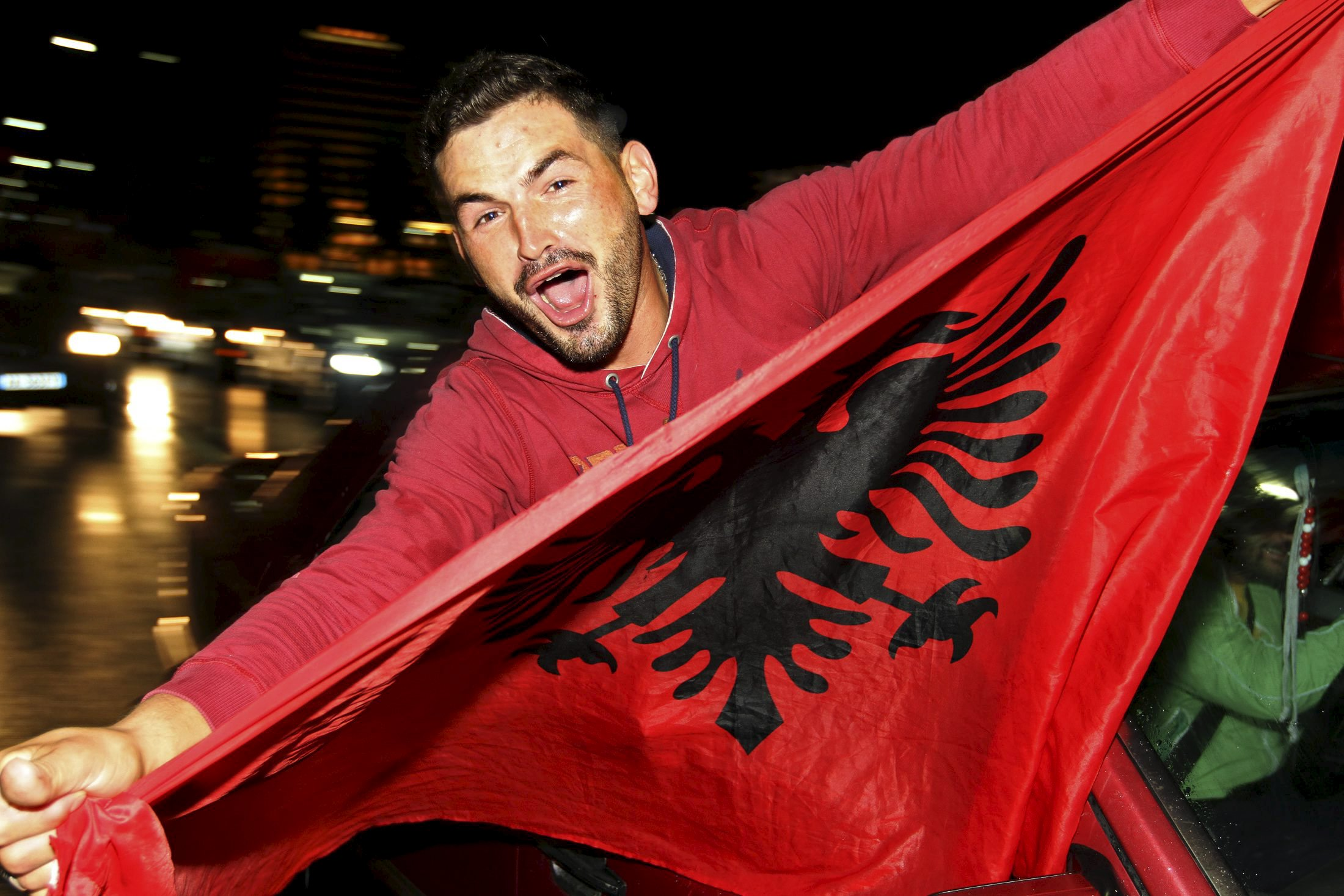 An Albanian soccer fan celebrates after Albania beat Armenia in their Euro 2016 Group I qualifying soccer match, in Tirana, Albania October 11, 2015. Albania qualified for Euro 2016, their first ever major tournament, when a 3-0 away win over Armenia clinched second place in Group I above Denmark on Sunday sparking wild celebrations across the country. REUTERS/Arben Celi