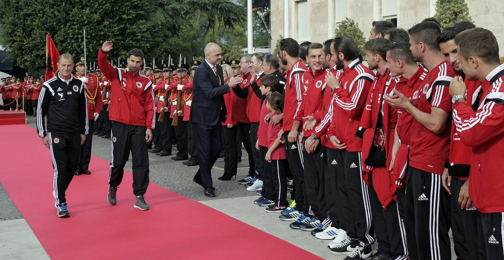 epa04975228 Albanian National soccer team is received by Albanian Prime Minister Edi Rama (C) accompanied by Albanian Head Coach Giovanni De Biasi (L) and Captain lorik Cana (C) in front of Government building in Tirana, Albania, 12 October 2015. Thousands of Albanians turned out in the capital Tirana to welcome the national football team after it secured the country's first-ever place at a major finals. Albania the previous day secured second spot in Euro 2016 qualifying Group I with a 3-0 win away to Armenia. EPA/FLORION GOGA