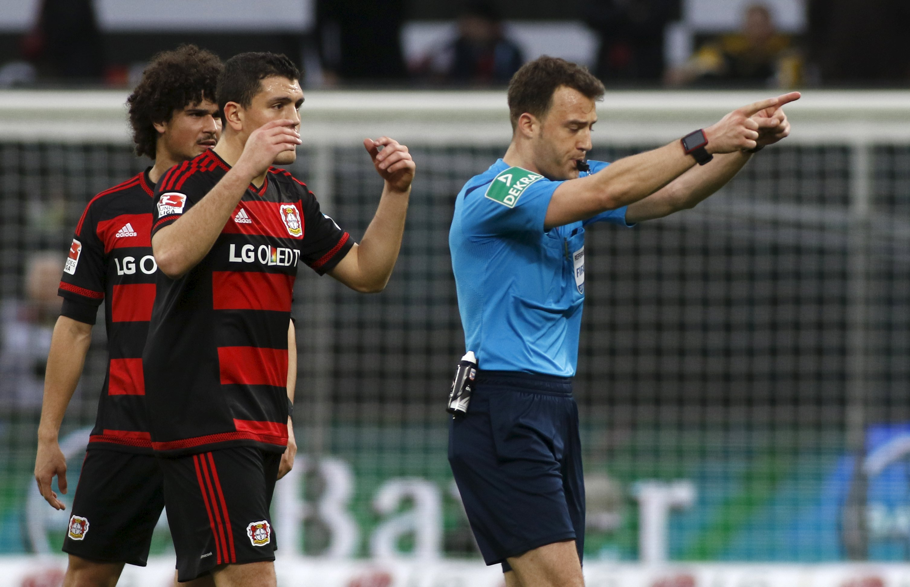 Football Soccer -- Bayer Leverkusen v Borussia Dortmund - German Bundesliga - BayArena , Leverkusen, 21/02/16 Referee Felix Zwayer and Leverkusen's Kyriakos Papadopoulos and Ramalho (L) react. REUTERS/Ina Fassbender DFL RULES TO LIMIT THE ONLINE USAGE DURING MATCH TIME TO 15 PICTURES PER GAME. IMAGE SEQUENCES TO SIMULATE VIDEO IS NOT ALLOWED AT ANY TIME. FOR FURTHER QUERIES PLEASE CONTACT DFL DIRECTLY AT + 49 69 650050