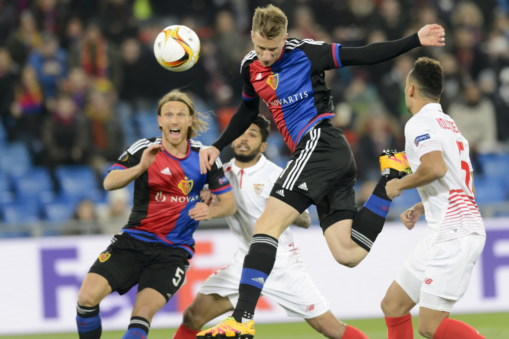 From left, Basel's Michael Lang, Sevilla's Benoit Tremoulinas, Basel's Marc Janko and Sevilla's Timothee Kolodziejczak fight for the ball during the UEFA Europa League Round of 16 first leg soccer match between Switzerland's FC Basel 1893 and Spain's Sevilla Futbol Club at the St. Jakob-Park stadium in Basel, Switzerland, on Thursday, March 10, 2016. (KEYSTONE/Laurent Gillieron)
