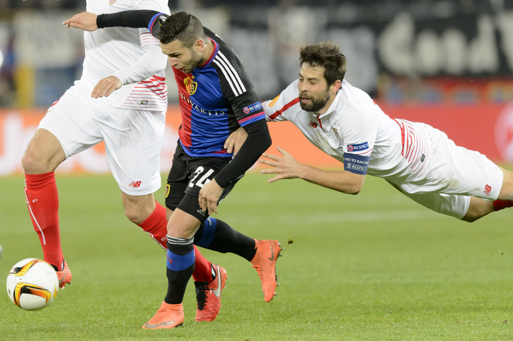 Basel's Renato Steffen, left, fights for the ball against Sevilla's Coke, right, during the UEFA Europa League Round of 16 first leg soccer match between Switzerland's FC Basel 1893 and Spain's Sevilla Futbol Club at the St. Jakob-Park stadium in Basel, Switzerland, on Thursday, March 10, 2016. (KEYSTONE/Laurent Gillieron)