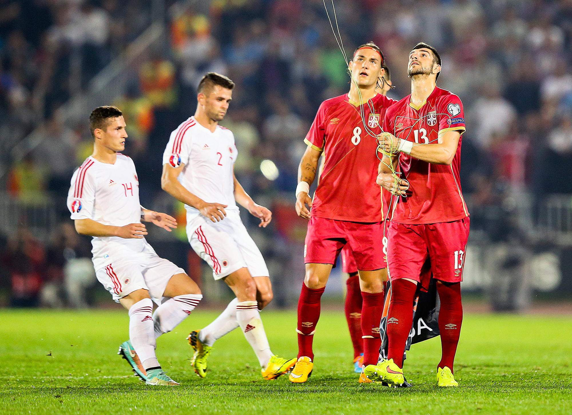 epa04447012 Serbian players try to recover a flag on the pitch before the Euro 2016 Group I qualifying match between Serbia and Albania was suspended, at the Partizan stadium in Belgrade, Serbia, 14 October 2014. The match was suspended after the flag Albanian symbols was flown above the stadium remote controlled by a drone which provoked a fight between players. EPA/SRDJAN SUKI