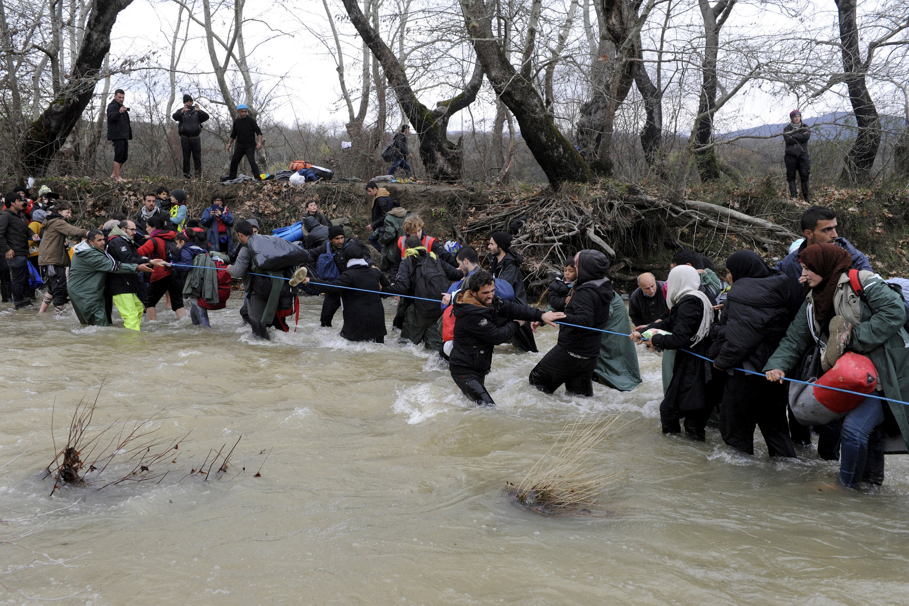 Migrants wade across a river near the Greek-Macedonian border, west of the the village of Idomeni, Greece, March 14, 2016. REUTERS/Alexandros Avramidis