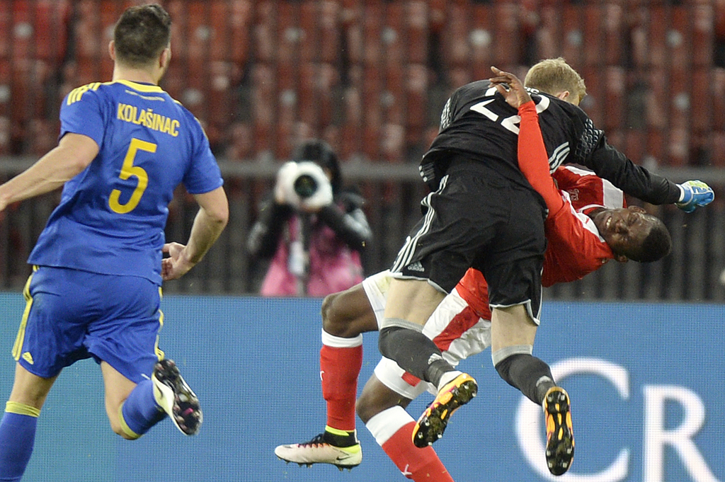 CORRECTS NAME OF GOALKEEPER --- Swiss Breel Embolo, right, and Bosnia Herzegovina's goalkeeper Jasmin Buric, center, collide during the friendly soccer match between Switzerland and Bosnia Herzegovina at the Letzigrund Stadium in Zurich, Switzerland, Tuesday, March 29, 2016. (KEYSTONE/Walter Bieri)