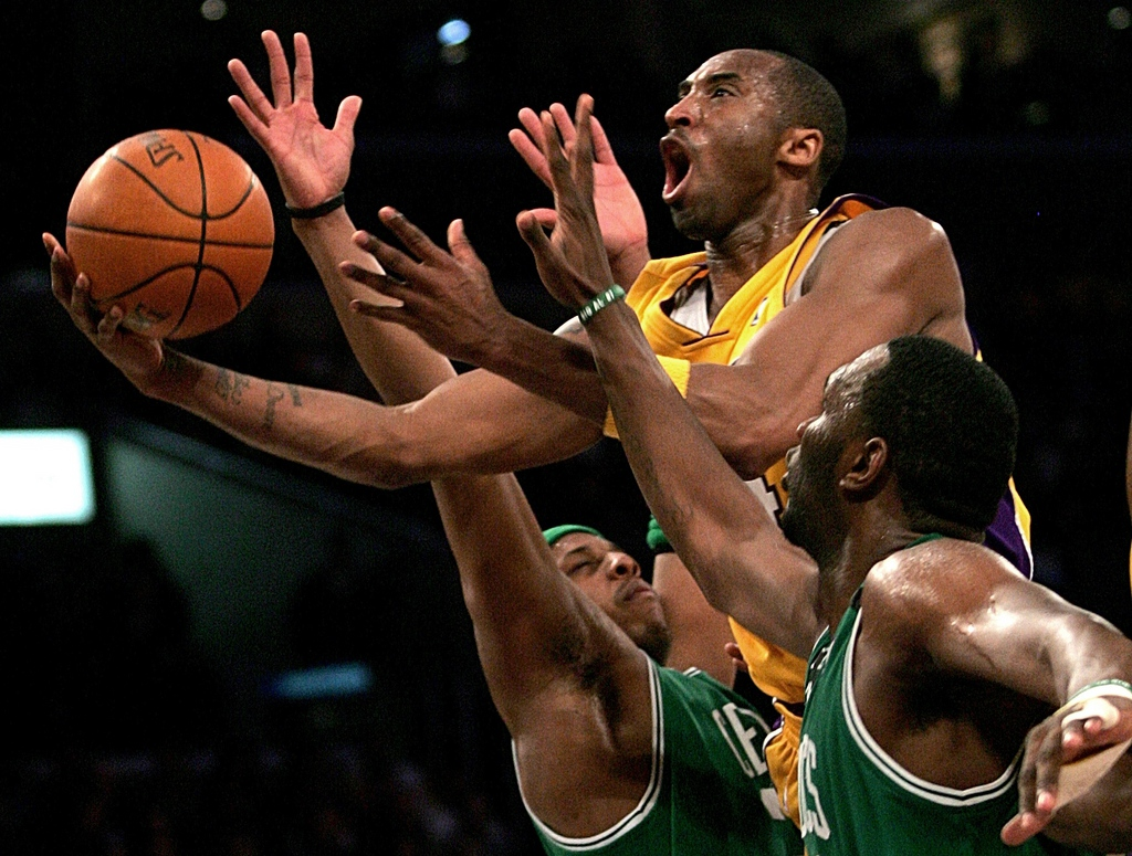 FILE - In this Feb. 23, 2007 file photo, Los Angeles Lakers' Kobe Bryant, top, goes up for a shot between the Boston Celtics' Paul Pierce, left, and Al Jefferson during the first half of an NBA basketball game in Los Angeles. After two decades spent dazzling the world, Bryant will end his basketball career at home with the Los Angeles Lakers on Wednesday night, April 13, 2016.(AP Photo/Branimir Kvartuc, File)