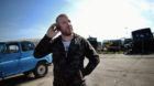 epa05238826 Bulgarian Dinko Valev (29), owner of a breakersyard for trucks and buses, uses his mobile phone while posing for