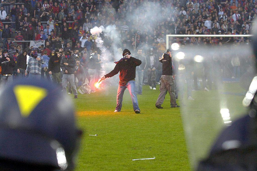 ZUR ENTSCHEIDUNG IN DER SCHWEIZER FUSSBALL-MEISTERSCHAFT DER SAISON 2005/06 AM 13. MAI 2006, ZWISCHEN DEM FCB UND DEM FCZ, STELLEN WIR IHNEN FOLGENDES BILDMATERIAL ZUR VERFUEGUNG - Des supporters sont decendu sur le terrain pour provoque la police, a la fin de la rencontre de football de superleage entre la FC Bale et le FC Zurich, ce samedi 13 mai 2006 au Stade Saint-Jacques de Bale - Basel Fans randalieren auf dem Spielfeld nach dem Fussball Meisterschaftsspiel der Super League zwischen dem FC Basel und dem FC Zuerich am Samstag, 13. Mai 2006, in Basel. Der FC Zuerich schlug Basel mit 1:2 Toren und holte sich den Meistertitel. (KEYSTONE/Sandro Campardo)