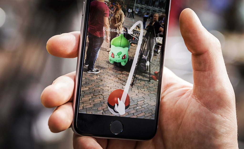 epa05424119 A close-up view of a gamer playing the Pokemon Go app on the Grote Markt in Haarlem, The Netherlands, in an image dated 13 July 2016. The game, that uses the GPS to locate the smartphone's location, has gained a huge popularity among smartphone users and added to the value of Nintendo that partly owns the franchise enterprise that makes Pokemon. EPA/REMKO DE WAAL