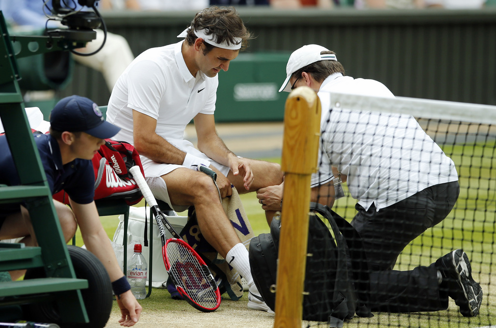 FILE - In this July 8, 2016, file photo, Roger Federer of Switzerland receives medical attention during his men's semifinal singles match against Milos Raonic of Canada at the Wimbledon Tennis Championships in London. Federer says he will miss the Rio Olympics and the rest of the tennis season to protect his surgically repaired left knee. Federer writes Tuesday, July 26, 2016, on his Facebook page that he will skip the Summer Games, where the tennis competition starts next week, and has been advised by doctors to remain sidelined for the remainder of 2016..(AP Photo/Alastair Grant, File)