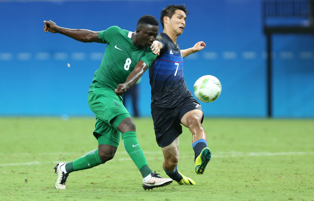 Nigeria's Oghenekaro Etebo strikes the ball to score as Japan's Riki Harakawa fails to stop him during a group B match of the men's Olympic football tournament between Japan and Nigeria at the Amazonia Arena, in Manaus, Brazil, Thursday, Aug. 4, 2016. (AP Photo/Michael Dantas)