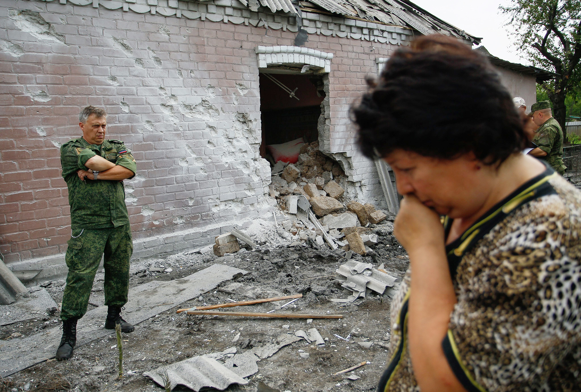 epa05450328 A woman reacts as a pro-Russian rebel stands next to a damaged house after the recent shelling, in Donetsk, Ukraine, 31 July 2016. EPA/ALEXANDER ERMOCHENKO