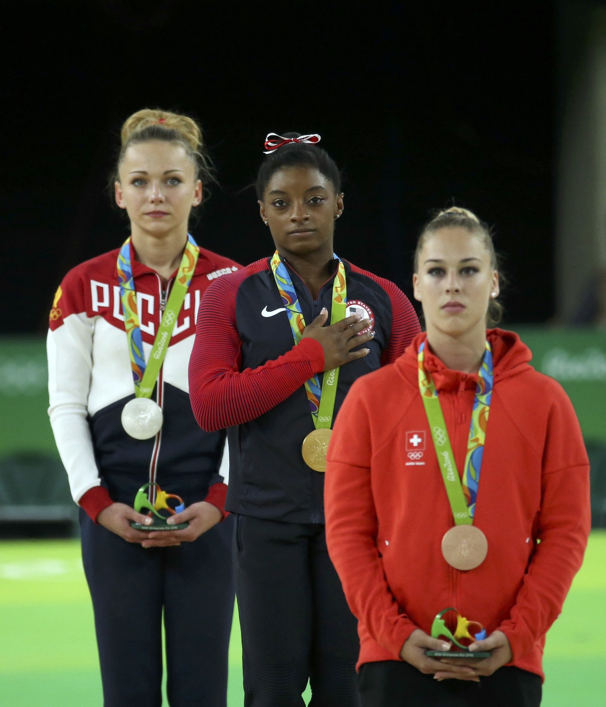 2016 Rio Olympics - Artistic Gymnastics - Victory Ceremony - Women's Vault Victory Ceremony - Rio Olympic Arena - Rio de Janeiro, Brazil - 14/08/2016. Simone Biles (USA) of USA, Giulia Steingruber (SUI) of Switzerland and Maria Paseka (RUS) of Russia listen to the USA anthem. REUTERS/Ruben Sprich FOR EDITORIAL USE ONLY. NOT FOR SALE FOR MARKETING OR ADVERTISING CAMPAIGNS.