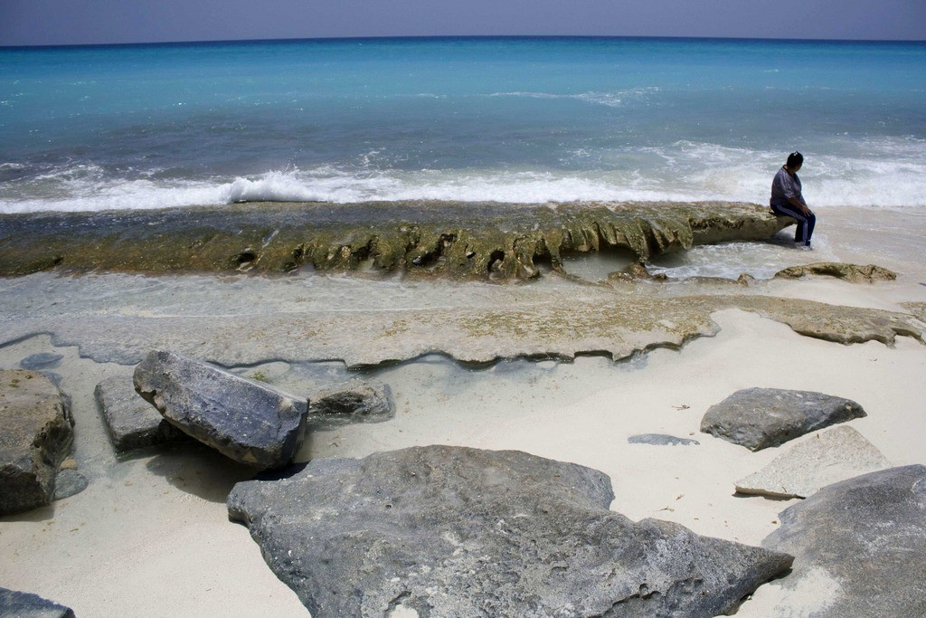 A woman sits on a heavily eroded beach in the resort city of Cancun, Mexico, Tuesday, July 21, 2009. The Mexican government a