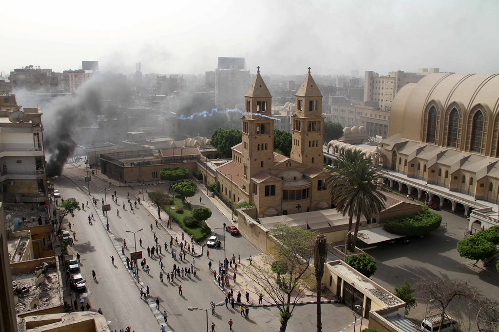 epa03652829 A general view shows smoke and tear gas rising during clashes outside the Abbassiya Cathedral following the funeral of Copts killed in violence the day before, in Cairo, Egypt, 07 April 2013. Clashes broke out on 07 April outside Cairo's main church at a funeral of four Egyptian Christians killed in violence with Muslims. The violence started when angry mourners chanted slogans against President Mohamed Morsi and his Muslim Brotherhood group. Unidentified assailants attacked the mourners outside the cathedral with shotguns, petrol bombs and stones. EPA/STR