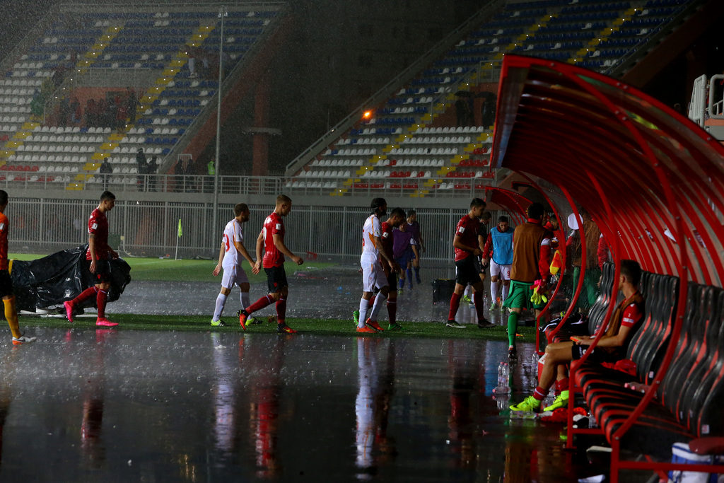 Players leave the pitch after their match was suspended due to heavy rain at the World Cup Group G qualifying match between Albania and Macedonia at the Loro Borici Stadium in Shkoder, northern Albania, Monday, Sept. 5, 2016. (AP Photo/Hektor Pustina)