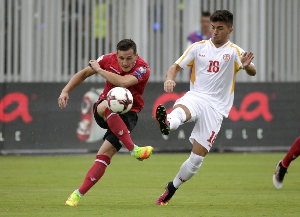 epa05527068 Albania's Taulant Xhaka (L) in action against Macedonia's Nikola Gjorgjev during the FIFA 2018 World Cup European qualifiers Group G soccer match between Albania and FYR of Macedonia at the 'Loro Borici' Stadim in Shkoder, Albania, 06 September 2016. The match was continued on 06 September after it was suspended on the previous night because of torrential rain. EPA/ARMANDO BABANI