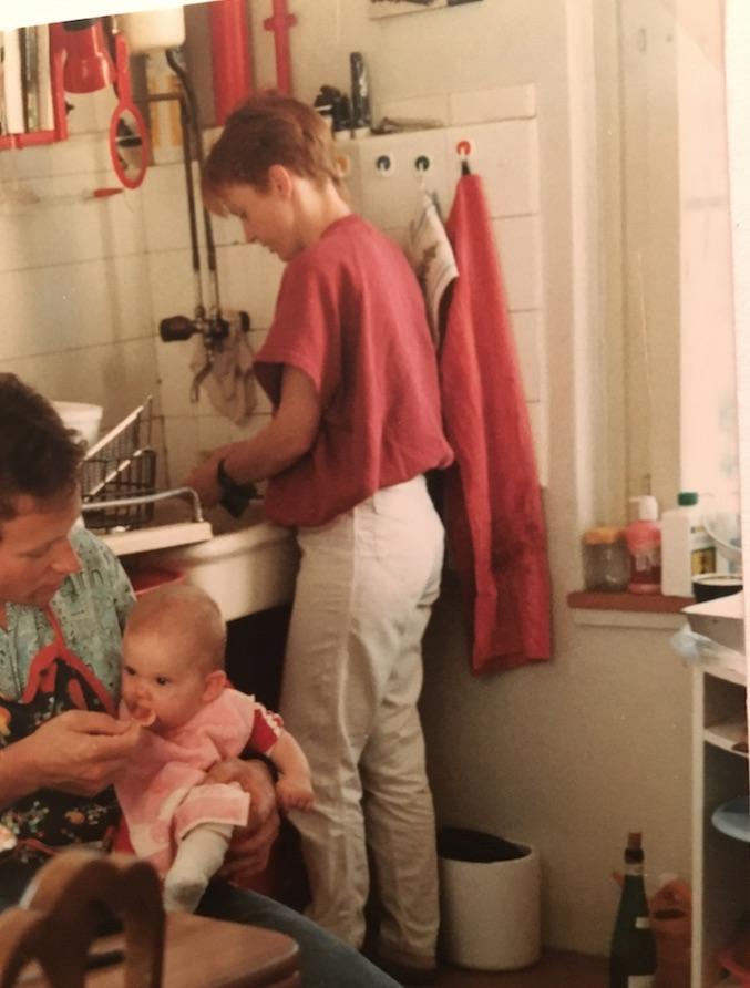 Damals eher an Brei als an Hose interessiert: Die Autorin beim Mittagessen mit Mom Jeans-Mami im Hintergrund.