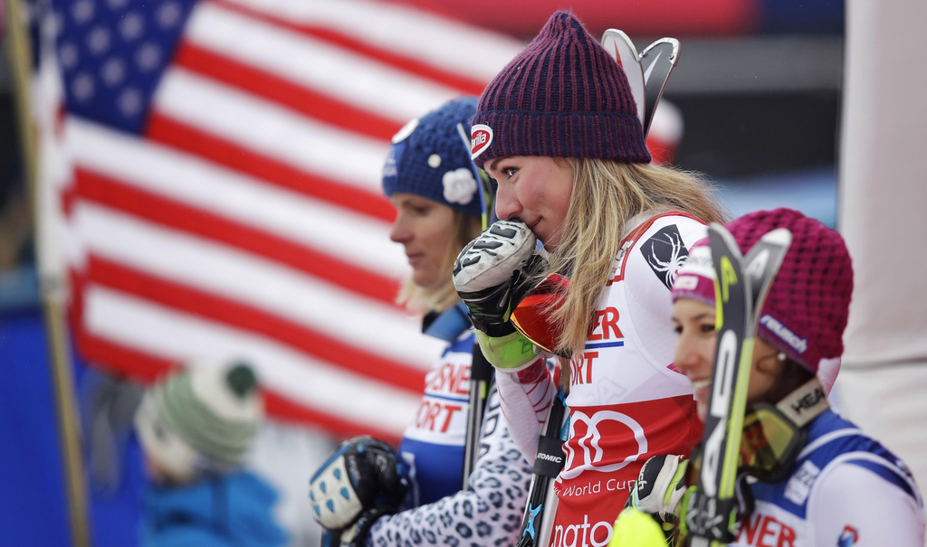 Mikaela Shiffrin, of the United States, holds her glove to her face and smiles towards her grandmother while standing on the podium after winning the alpine skiing women's World Cup slalom in Killington, Vt., Sunday, Nov. 27, 2016. (AP Photo/Charles Krupa)