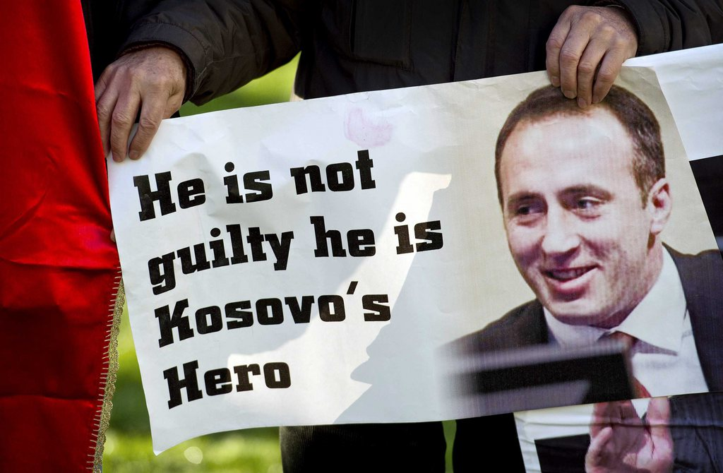 epa03490152 A supporter of the former commander of the Kosovo Liberation Army Ramush Haradinaj with a sign in front of the International Criminal Tribunal for the former Yugoslavia at the Hague, Netherlands, 29 November 2012. Media reports on 29 November 2012 state that the UN war crimes tribunal has cleared Ramush Haradinaj after a retrial in The Hague. EPA/KOEN VAN WEEL / POOL
