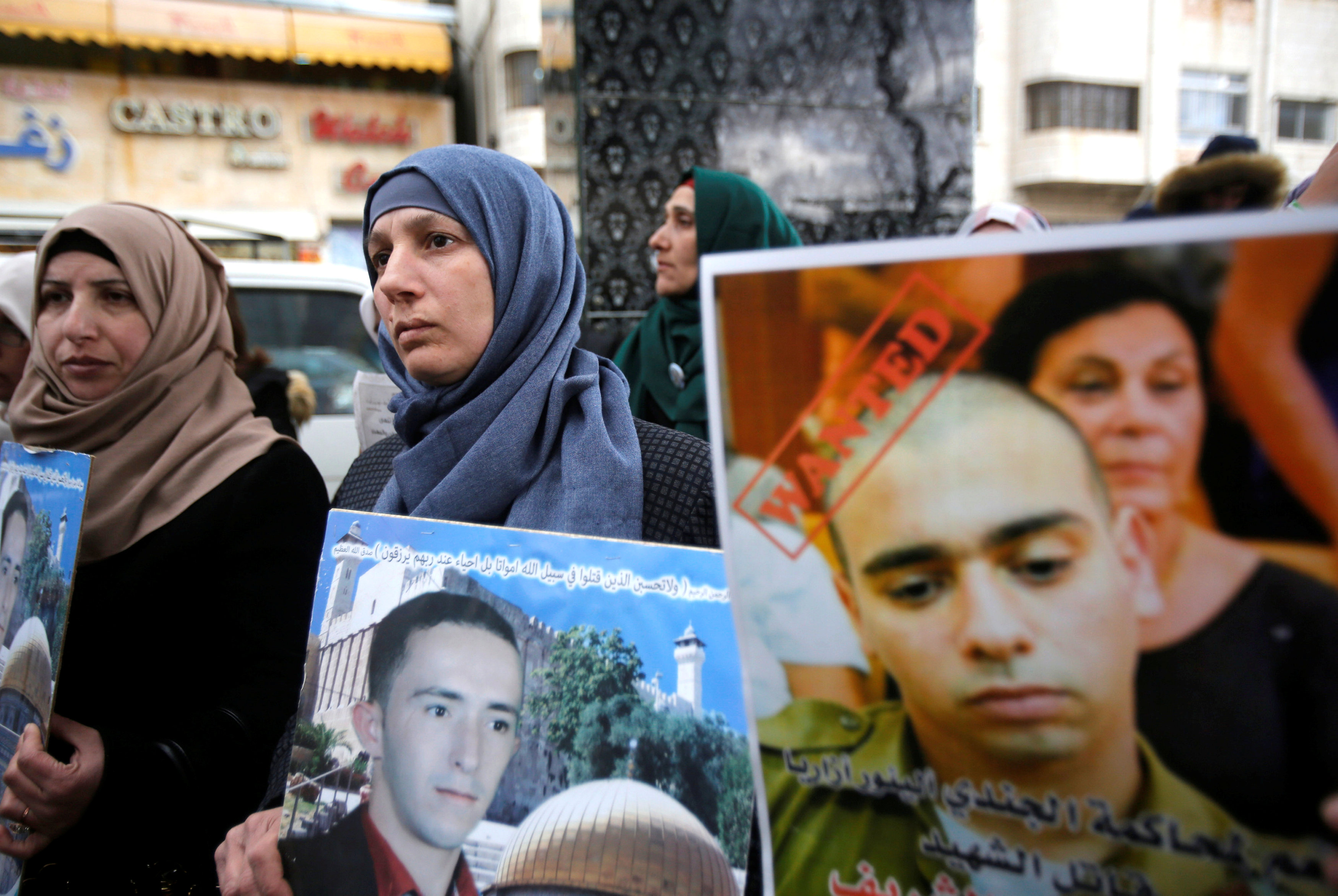 The mother (C) of Palestinian assailant Abdel Fattah al-Sharif holds his poster as another woman holds a poster of Israeli soldier Elor Azaria, who is charged with manslaughter by the Israeli military, during a protest in the West Bank city of Hebron January 4, 2017. REUTERS/Mussa Qawasma