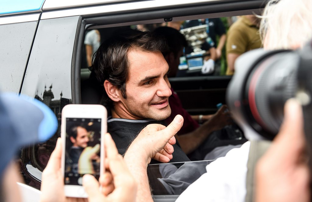 epa05760999 Switzerland's Roger Federer looks on from the window of a vehicle as he leaves after a photo shoot with his Australian Open Men's Singles trophy at Carlton Gardens in Melbourne, Australia, 30 January 2017. Federer defeated Rafael Nadal of Spain in their final match. EPA/FILIP SINGER